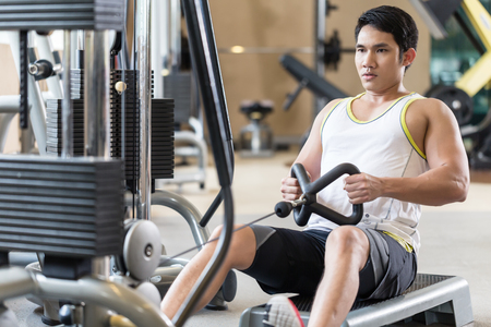Portrait of a determined handsome young man looking forward while rowing at the cable machine during workout for back muscles in a modern fitness club Stock Photo