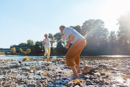 Full length of a funny senior couple playing with water at the river while enjoying their happy relationship in a sunny day of summer Archivio Fotografico