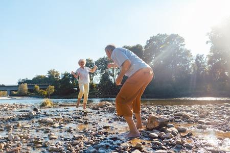 Volle Länge eines lustigen älteren Paares, das mit Wasser am Fluss spielt, während sie ihre glückliche Beziehung an einem sonnigen Sommertag genießen