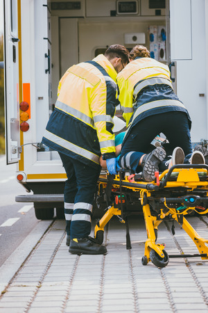 Paramedic on stretcher fighting for life of injured woman giving cardiac massage