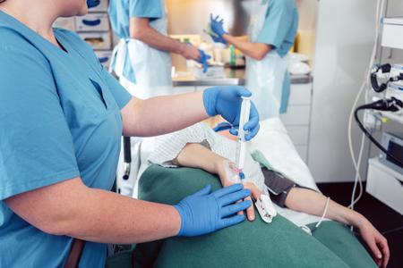 Verpleegster die anesthesie geeft aan patiënt die op endoscopieonderzoek in het ziekenhuis wacht
