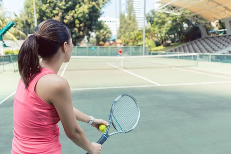 Rear view of a fit young woman wearing pink sleeveless top while playing tennis on a professional court in the city