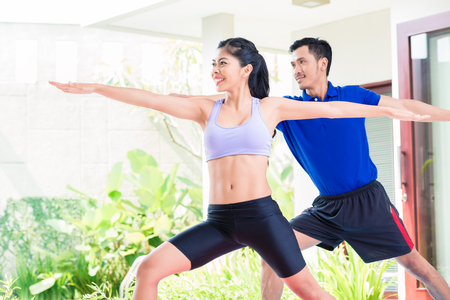 Happy Asian fitness couple at sport workout in tropical home