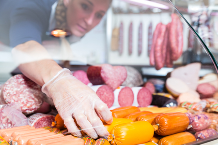 Woman putting sausages and meat in butcher shop display, close-up Foto de archivo