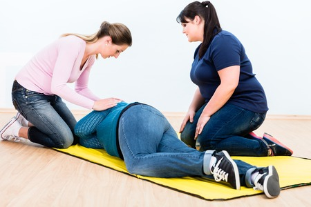 Women in first aid training learning to position injured person