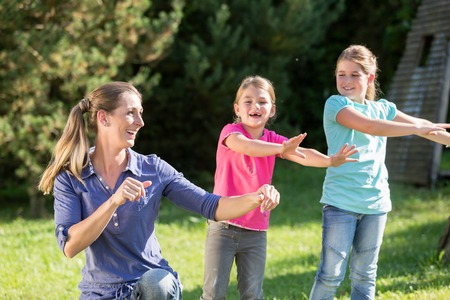 Happy mother with children daughters doing dance exercise outdoors
