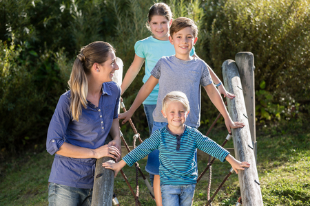 Happy family with kids playing on adventure playground Stock Photo