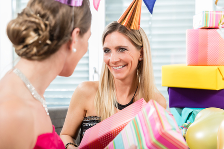 Two cheerful adult women and best friends holding funny party horns and a birthday cake while celebrating together indoors in a decorated room