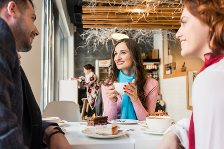 Three best friends smiling while relaxing together with delicious cakes and coffee cups in a trendy cafeteria