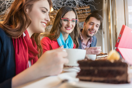 Three cheerful colleagues watching together a funny video on laptop during coffee break in a trendy coffee shop Stock Photo
