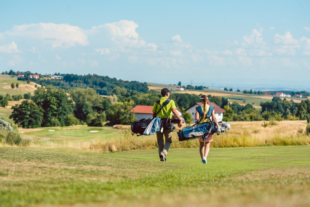 Full length rear view of a couple carrying professional golf bags, while walking on green field towards the golf course in a sunny day of summer Stock Photo