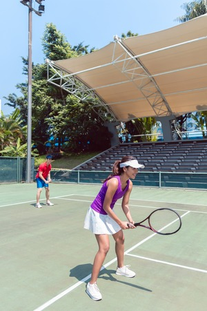 Full length of a confident female tennis player smiling while waiting to hit the ball during doubles match on a professional modern court Stock Photo