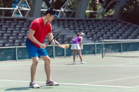 Side view of an Asian tennis player ready to serve at the beginning of a doubles mixed match on a professional tennis court