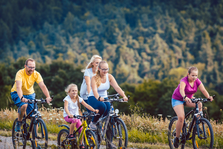 Family riding their bicycles on afternoon in the summer countryside Stock Photo