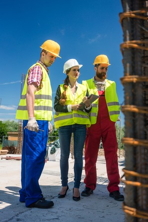 Female manager or architect between two workers supervising the work in progress on the construction site of a building with reinforcing steel structure Stock Photo