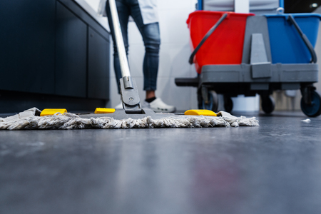 Niskie ujęcie sprzątaczki myjącej podłogę w toalecie obok swojego wózka Zdjęcie Seryjne