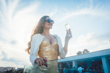 Woman having champagne at summer party with villa in the background Stock Photo