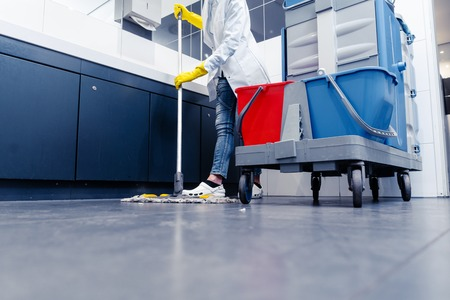Low shot of cleaning lady mopping the floor in restroom beside her trolley Stock Photo