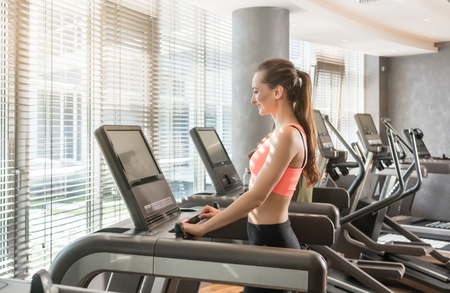 Young woman running on treadmills during workout session in the gym