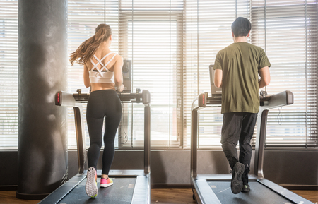 Full length rear view of young man and woman running on treadmills during workout session at the gym