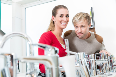 Low-angle portrait of a happy couple choosing a new faucet for their bathroom in a modern sanitary ware shop with high-quality products