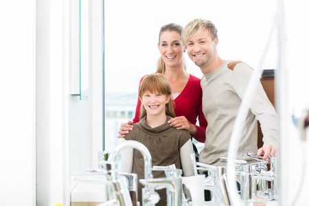 Portrait of a happy family with one child looking at camera, while posing together in the interior of a modern sanitary ware shop with various bathroom faucets for sale Stock Photo
