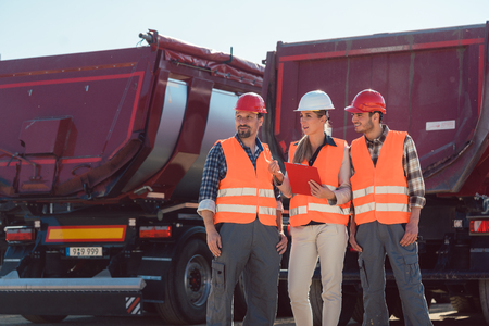 Truck drivers and dispatcher talking in front of lorries in freight forwarding company Stock Photo