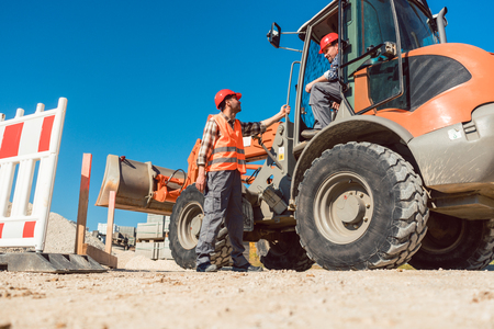 Construction worker starting road works on site with machine Stock Photo