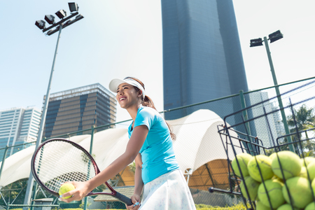 Low-angle view a cheerful beautiful woman ready to serve while playing tennis in a developed city with modern facilities Stock Photo