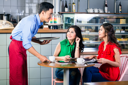 Side view of a handsome and polite waiter smiling while serving coffee at the table of two beautiful young women in a trendy coffee shop