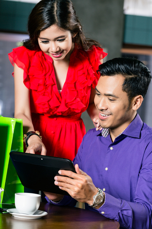 Young Asian couple watching a funny video or looking at pictures on a tablet connected to the internet in a trendy cafeteria