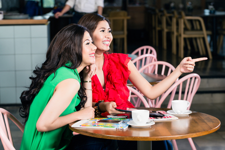 Two female best friends talking and sharing memories while drinking together a cup of coffee in a trendy location Stock Photo