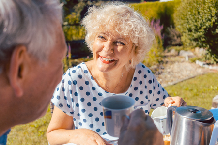 Happy elderly woman and man eating breakfast sitting in their garden outdoors in summer, eating bread rolls and drinking coffee Stock Photo