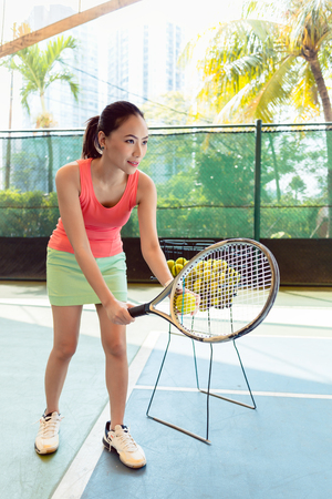 Beautiful Asian tennis player looking forward with concentration while holding the racket and the ball before serving at the beginning of the match Stock Photo