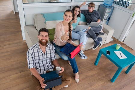 Happy young people laughing while sharing a collaborative office space as co-workers in a modern hub with WI-FI wireless network for digital nomads