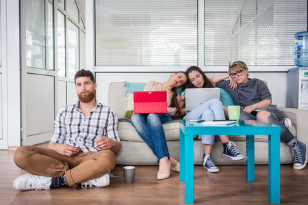 Depressed and sleepy young freelancers experiencing the disadvantages of self-employment through exhaustion or lack of contracts in a co-working office space Stock Photo