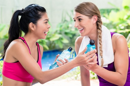 Asian woman and personal trainer at sport exercise in front of tropical garden