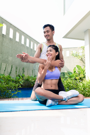Asian woman with trainer at fitness workout in front of tropical pool