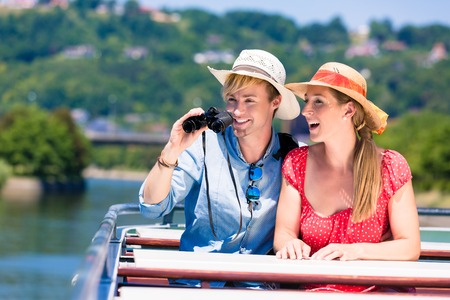 Happy couple on river cruise wearing sun hats in summer