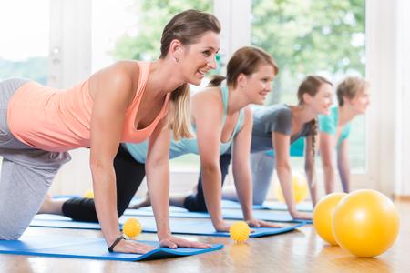 Happy moms in postnatal regression course doing yoga asana