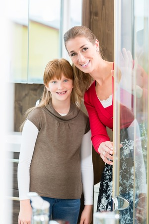 Cheerful woman with her daughter looking at a shower cabin in the showroom of a sanitary ware shop with modern bathroom fixtures for sale