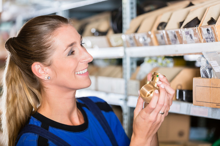 Side view close-up portrait of a happy blue-collar worker holding a high-quality pipe fitting accessory in a modern sanitary ware shop