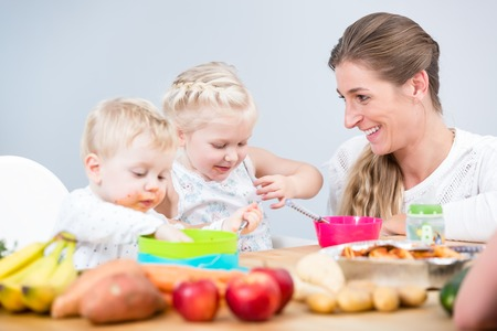 Portrait of a happy mother of two children sitting at table while watching them during a nutritious meal with organic ingredients at home Stock Photo