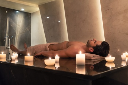 Young man relaxing on massage table surrounded by scented candles at Asian spa and wellness center Stock Photo
