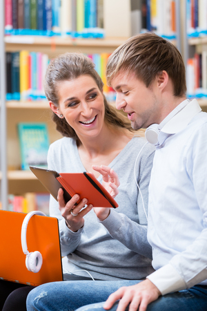 Woman and man with laptop and phone in library reading and listening Stock Photo