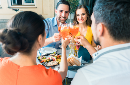 Four friends holding stemmed wine glasses while toasting together with a cold refreshing alcoholic drink during a delicious lunch at the restaurant