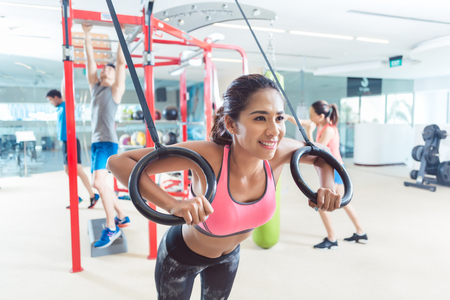 Cheerful fit young woman exercising with gymnastic rings during routine workout in a trendy fitness center with modern equipment for functional training Stock Photo