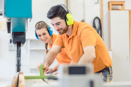 Carpenter man and woman working in workshop as a team Stock Photo