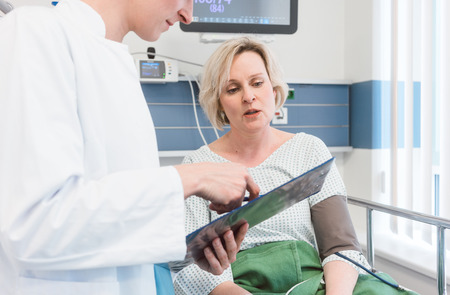 Doctor discussing treatment results with patient in intensive care unit of hospital