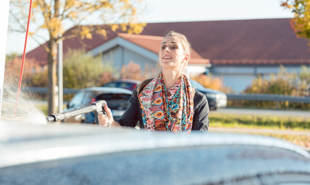 Woman using high pressure nozzle to clean and wash her car